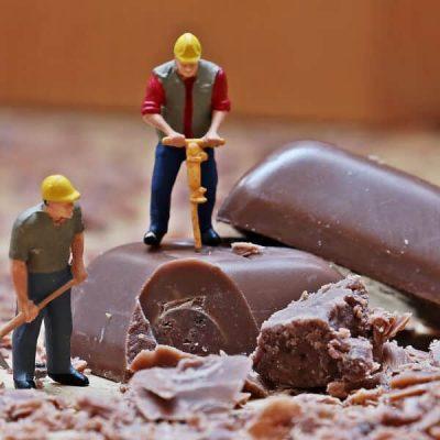 2 Trabajadores de plástico trabajando con pala y taladradora sobre una pastilla de chocolate de gran tamaño en comparación. Simboliza el trabajo mano a mano de consultoría de marketing online