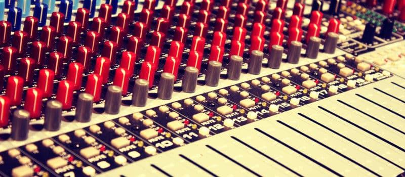 Se muestra un primer plano de una parte de una mesa de mezclas de sonido